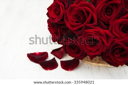 Basket with Fresh Red roses on a old wooden background
