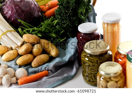 Basket with fresh vegetables versus canned vegetables in jars. Studio shot. White background. Copy space. - stock photo