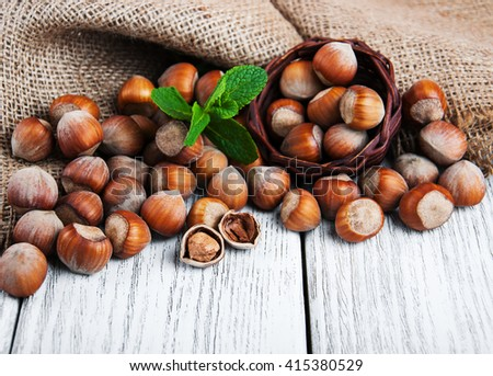 Basket with hazelnuts on a old wooden table - stock photo