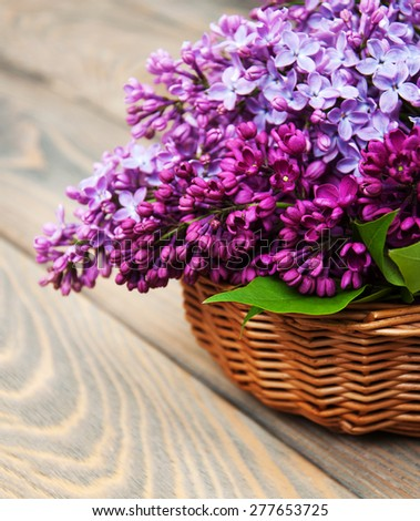 Basket with lilac flowers on a wooden background - stock photo