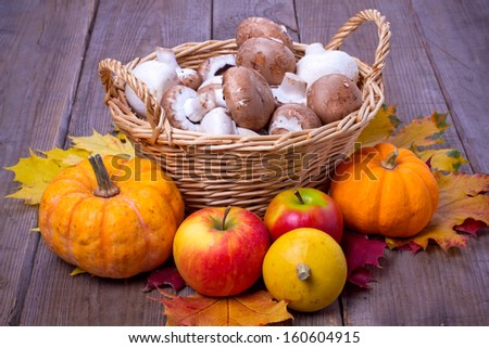 Basket with mushrooms and pumpkins, apples with leaves over wooden background - stock photo