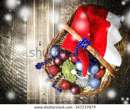 Basket with New Year's toys and garlands on wooden texture with snowfall - stock photo