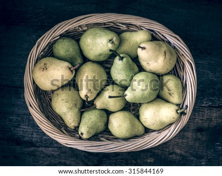Basket with pears on a rustic wooden  table - stock photo