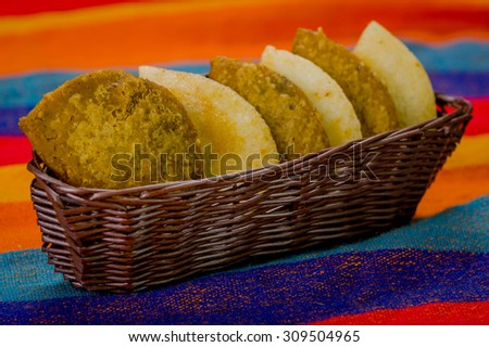Basket with six empanadas neatly placed inside sitting on latin colorful table cloth. - stock photo