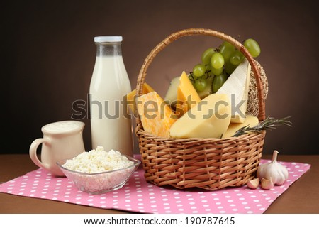 Basket with tasty dairy products on wooden table, on dark brown background - stock photo