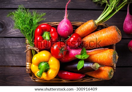Basket with various vegetables on the wooden table in the kitchen - stock photo
