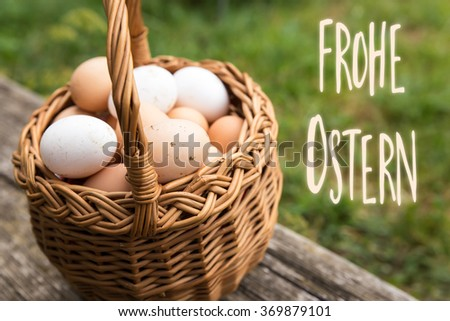 basket with white and brown bio eggs, green meadow in the background, german words frohe ostern which means happy easter - stock photo