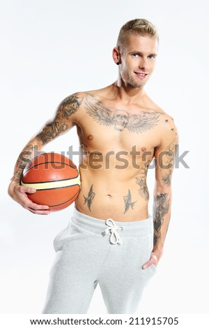 basketball  Attractive young boy with an orange ball for basketball, tattooed in sports trousers  - stock photo