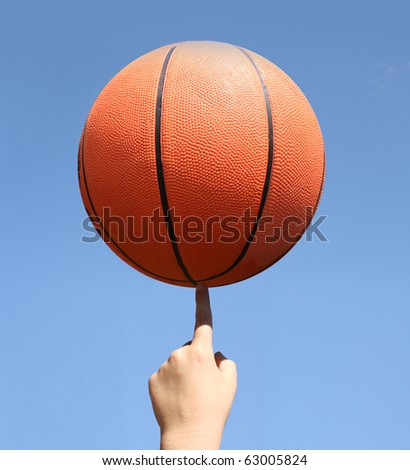 basketball balanced on a finger - stock photo