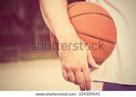 Basketball ball on a bench with defocused players in the background. - stock photo