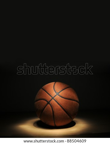 Basketball ball on the parquet with black background (light painting technique)