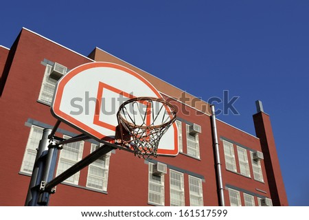 Basketball Basket in front of a school building against clear blue sky - stock photo