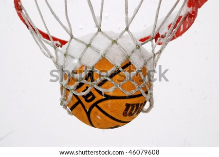 Basketball frozen in the net during a winter storm.