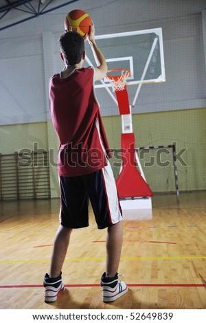 basketball game playeer shooting on basket indoor in gym - stock photo