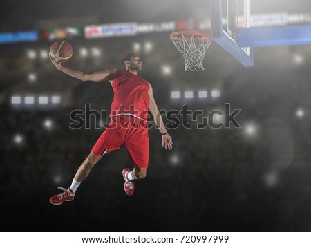basketball game sport player in action in front of big modern basketball arena with flares and lights