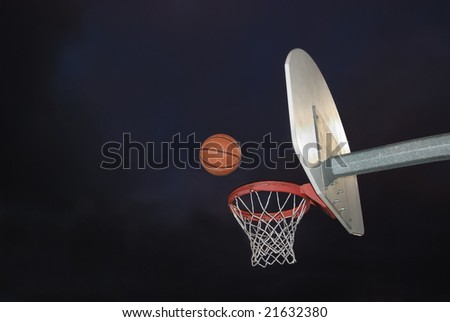 Basketball going into the hoop at an outdoor court in the dark - stock photo