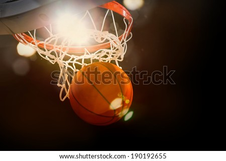 Basketball going through the basket at a sports arena (intentional spotlight) - stock photo
