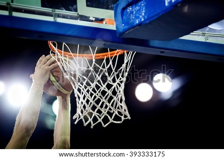 Basketball going through the hoop at a sports arena (intentional spotlight) - stock photo