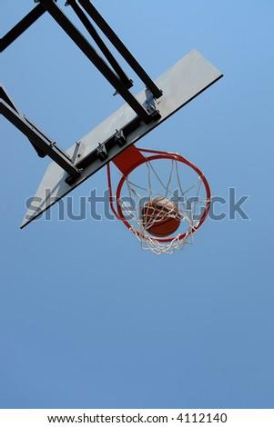 Basketball hitting the backboard net against clear blue sky - stock photo