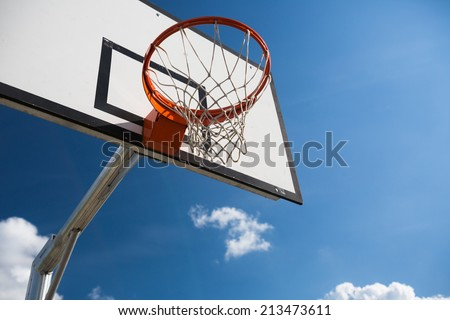 Basketball hoop against  lovely blue summer sky with some fluffy white clouds - stock photo