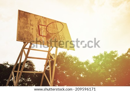 Basketball hoop and wood backboard at sunset (vintage style) - stock photo