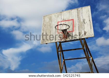 Basketball hoop and wood backboard with blue sky - stock photo