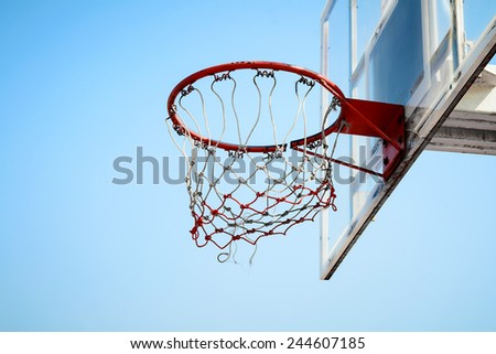 Basketball hoop in outdoor basketball field with blue sky - stock photo