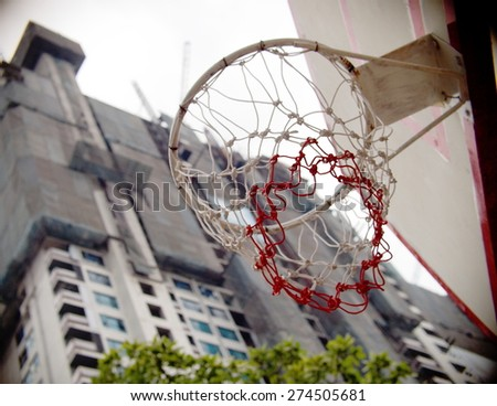basketball hoop near construction site standing outdoor in a community park with green surrounding for village children to play and have exercise as free sport and healthy infrastructure concept - stock photo