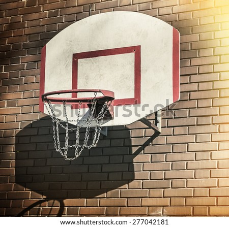 Basketball hoop on a brick wall. Focus on the grid ring. Processing in grunge style - stock photo