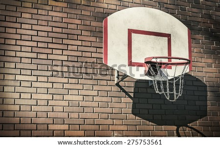 Basketball hoop on a brick wall. Focus on the grid ring. The empty space can be used for text. toned image - stock photo