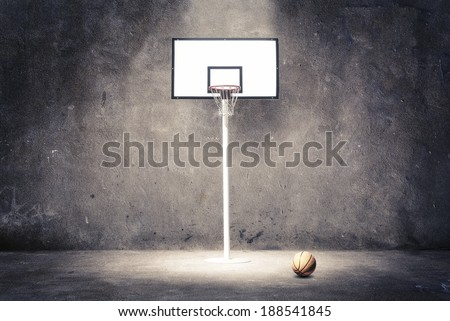 Basketball hoop on a textured wall with a ball. - stock photo