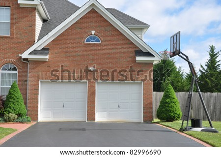 Basketball Hoop on Driveway in front of Suburban Home Two Car Garage Doors on Sunny Day - stock photo