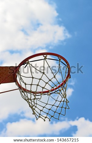 Basketball hoop, side view against blue sky.