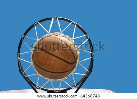 Basketball in the net against clear blue skies - concept of a successful endeavor - stock photo