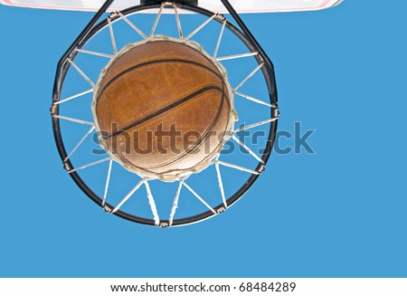 Basketball in the net against clear blue sky - concept of a successful endeavor - stock photo