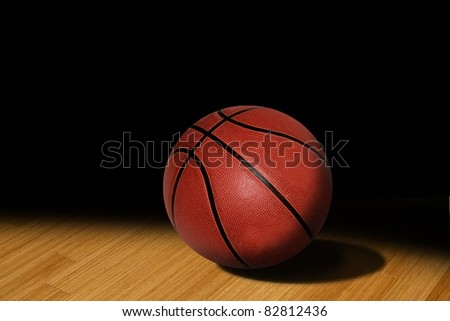 basketball in the spotlight on court - stock photo