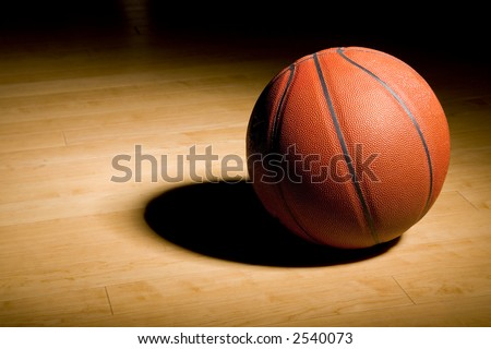 basketball in the spotlight resting on the hardwood floor