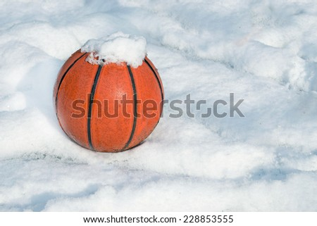 basketball on a playground covered by snow - stock photo