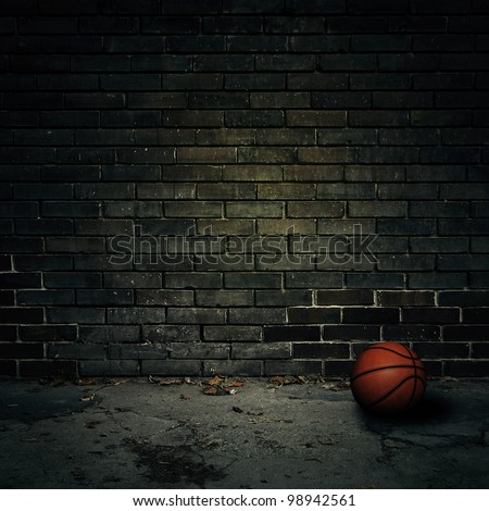 Basketball on concrete with brick wall
