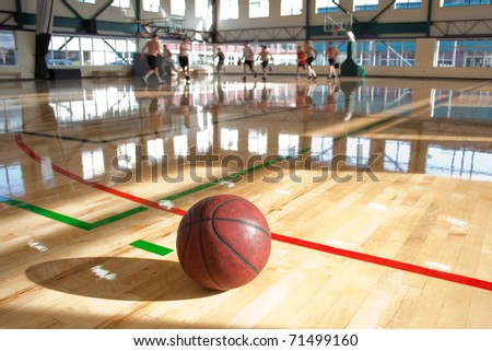 basketball on floor beside game action - stock photo