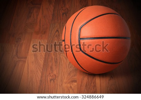 Basketball on hard wood dark background as a symbol of sport and exercise, leisure activities, team players with dribbling and passing the ball in a competitive match - stock photo
