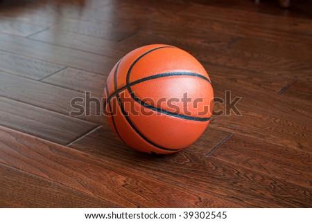 Basketball on the hardwood basketball floor in a stadium - stock photo