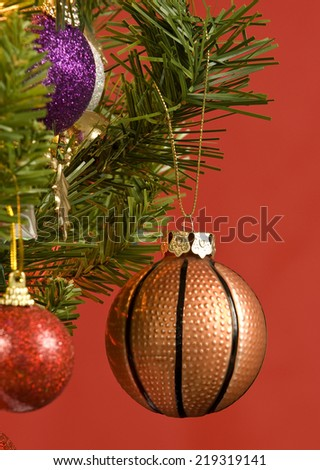Basketball Ornament Hanging On Christmas Tree Vertical Shot Red Background