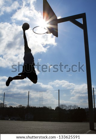 Basketball Player Dunk Silhouette - stock photo