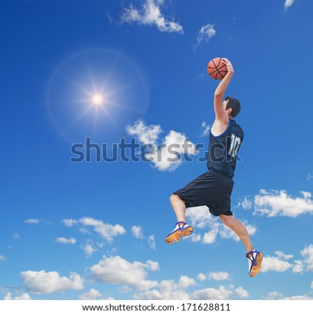 basketball player dunking in the sun - stock photo