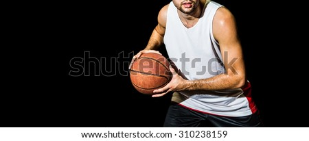 Basketball player holding a ball against dark background - stock photo