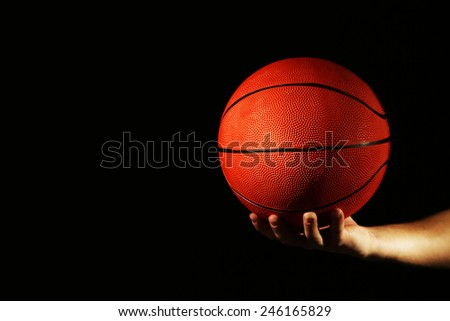 Basketball player holding ball, on dark background - stock photo