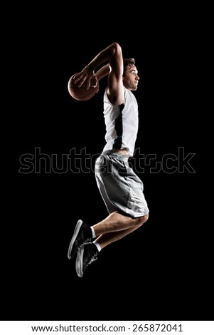 Basketball player in action isolated black background - stock photo
