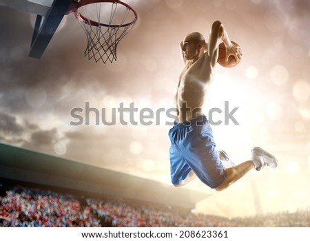 Basketball player in action on background of sky and crowd  - stock photo