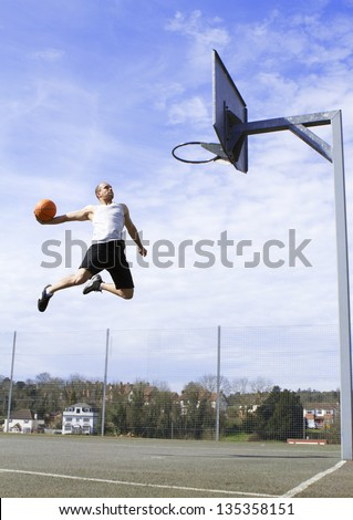 Basketball Player in mid air about to Slam Dunk - stock photo